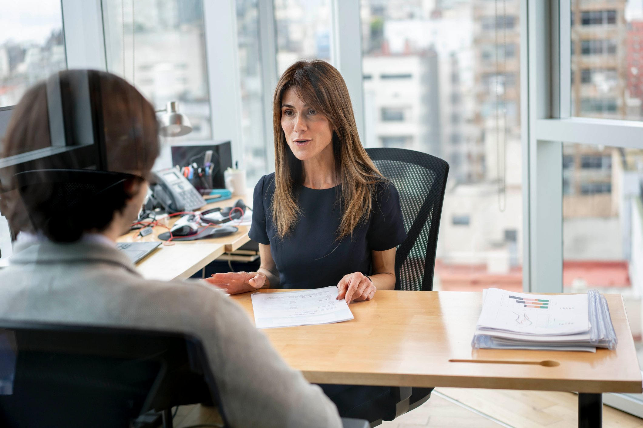 Woman at desk, in high-rise office, talking to man