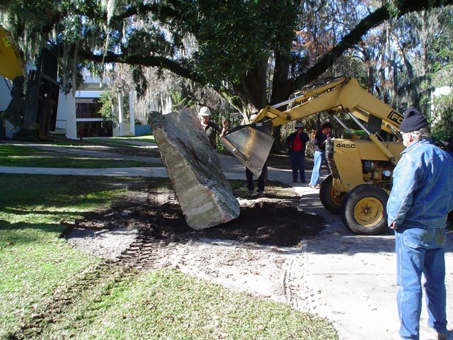 Backhoe installing marble rock