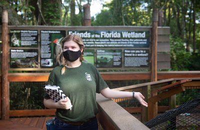 person on bridge in mask with florida wetland sign behind her